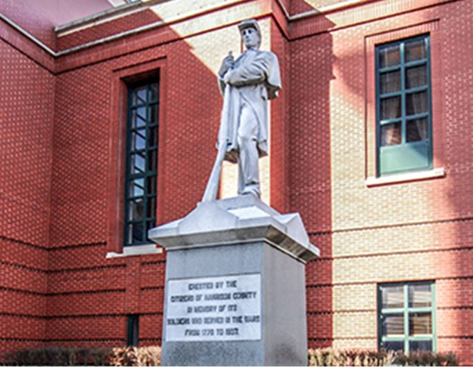 statue of man holding rifle in front of brick building